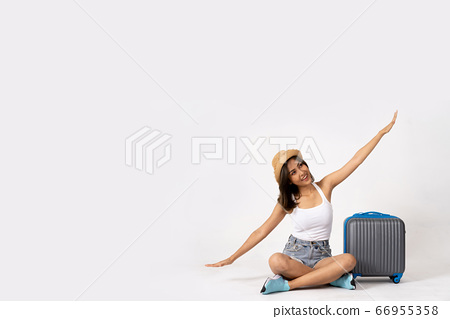 Young bruntte girl traveler with luggage case and summer hat flying like airplane in white isolated background. 66955358