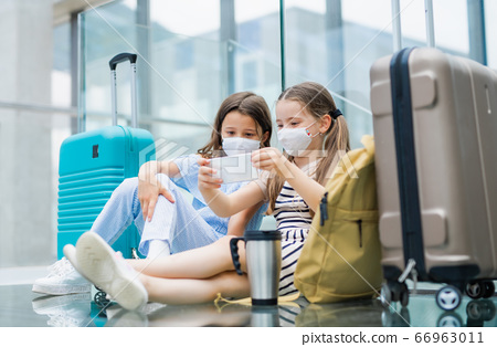 Small children with smartphone going on holiday, wearing face masks at the airport. 66963011