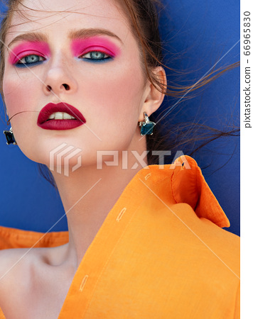 Fashion portrait of stunning woman with bright makeup  and fluttering hair wearing orange shirt.  66965830