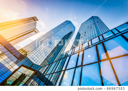 Modern skyscrapers in business district at sunset against blue sky 66967383