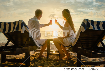 couple drinking cocktails on beach during vacation or honeymoon in tropics 66967790