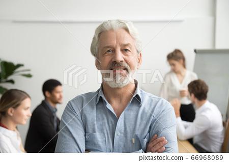 Confident senior businessman leader looking at camera, team at b 66968089