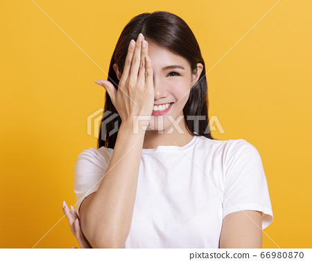 smiling young woman hand cover eye 66980870