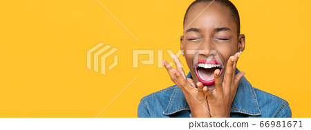 Panoramic close up portrait of ecstatic young African American woman screaming 66981671
