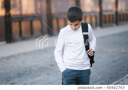Teenage boy take out a wireless headphones and put then into the ears. Young boy in white shirt with backpack. Boy listen music 66982763