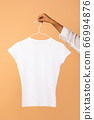 Female Hand Holding Clothes Hanger With White T-Shirt, Beige Background 66994876