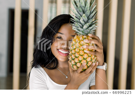 Resting at home. Charming smiling african young woman hiding half of face with fresh pineapple, while standing over wooden decorations at cozy living room at home. Summer, fruits and people concept 66996225