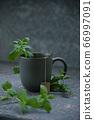 Mug with hot tea, mint leaves near a cup. 66997091