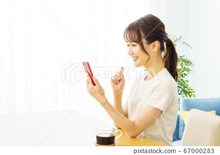 一個操作智能手機的女人 67000283