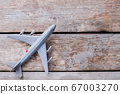Toy plastic airplane on the old vintage table. 67003270