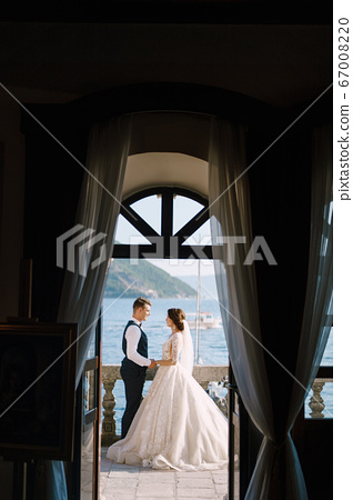 The bride and groom are standing on the balcony of the hotel overlooking the sea, a look through the open old window. Fine-art wedding photo in Montenegro, Perast.  67008220