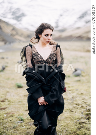 Close-up portrait of a bride in a black dress with a black coat and rude make-up. Stands in a field with yellow grass, against the backdrop of a snowy mountain. Destination Iceland wedding.  67008307