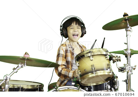 A cute Asian boy is enjoying playing the drums in a music classroom.  67010694