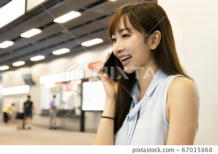 young woman talking on the phone in  train station 67015868