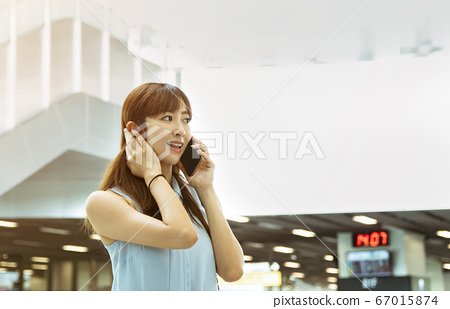 young woman talking on the phone in  train station 67015874