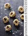 Raw italian tortellini on the wooden table 67022203