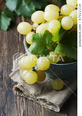 Yellow sweet grape on the wooden table 67022219