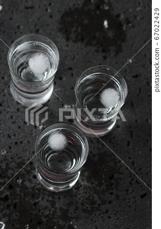 A glass of vodka on the black table 67022429