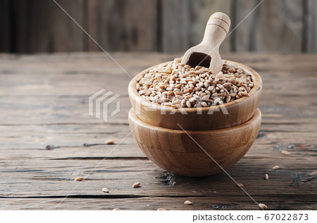 Raw pearl barley on the wooden table 67022873