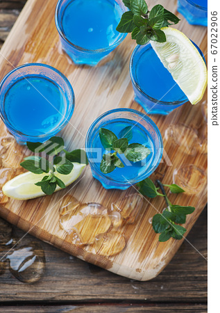 Blue curacao liqueur with lemon on the wooden 67022906