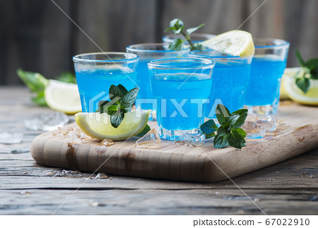 Blue curacao liqueur with lemon on the wooden 67022910