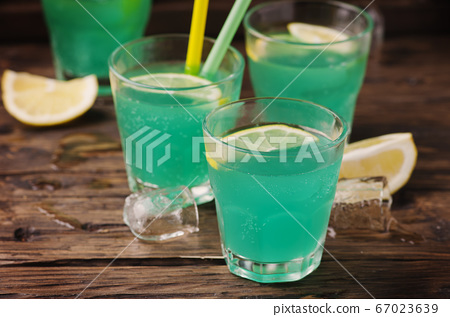 Green cocktail with lemon and ice on the wooden 67023639