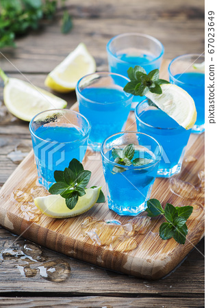 Blue curacao liqueur with lemon on the wooden 67023649