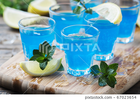 Blue curacao liqueur with lemon on the wooden 67023654