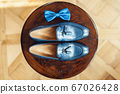 Blue shoes and bow tie on a wooden round stool. Accessory for formal dress. Symbol of elegance and fashion for men. 67026428