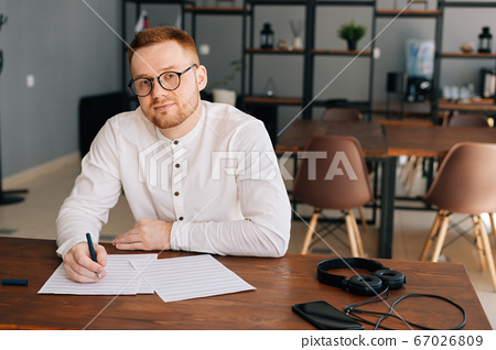Handsome young composer wearing stylish eyeglasses is sitting at the desk with paper sheet music 67026809