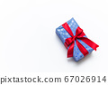 Blue gift box with red ribbons isolated on white 67026914