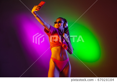 Beautiful seductive girl in fashionable swimsuit on disco bicolored neon studio background in neon light. Summer, resort, fashion and weekend concept 67028184
