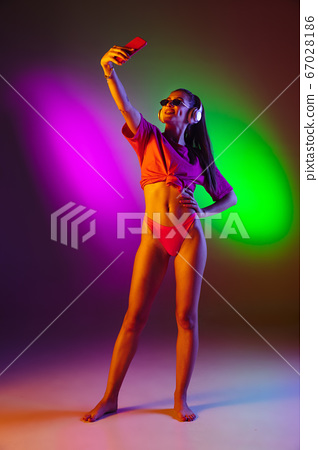 Beautiful seductive girl in fashionable swimsuit on disco bicolored neon studio background in neon light. Summer, resort, fashion and weekend concept 67028186