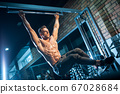 young bodybuilder with perfect body pull up with gym bar 67028684