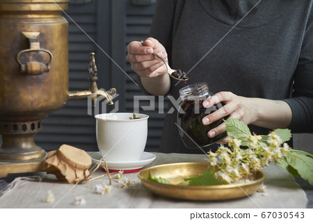 Side view of female hands puts homemade jam in cup 67030543