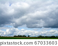 Landscape with clouds over fields and a forest in 67033603