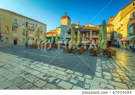 Promenade with street cafe at sunrise in Trogir, Dalmatia, Croatia 67034004