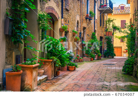 Retro stone houses decorated with colorful flowers, Pienza, Tuscany, Italy 67034007