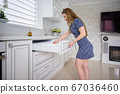 Young woman at luxury modern classic white kitchen interior 67036460