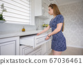Young woman at luxury modern classic white kitchen interior 67036461