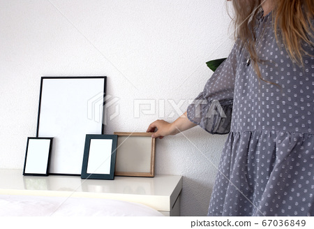 Woman holding empty photo or picture frame in a modern room near white wall, scandinavian design, retro interior 67036849