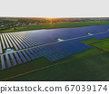 Aerial drone view into large solar panels at a 67039174
