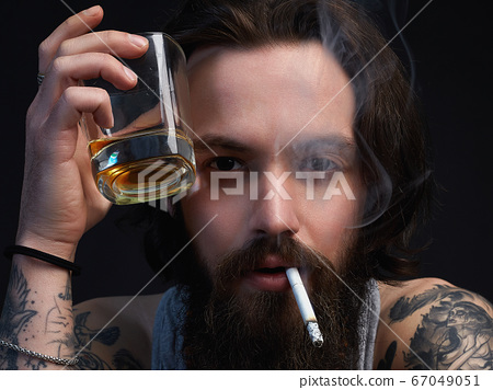 smoking hipster boy with beard and tattoo 67049051