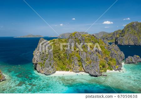 Aerial panoramic view of a tiny tropical island with beach, coral reef and sharp limestone cliffs. Shimizu Island, El Nido, Palawan 67050638