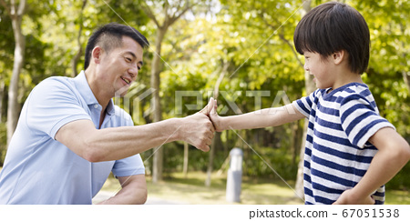 asian father and son making a deal by pressing thumbs together 67051538