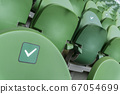 Empty plastic seats in a stadium. Stickers intended to promote social distancing in the arena. 67054699