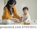 Baby and mother playing with blocks 67055631