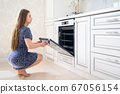 Young woman at luxury modern classic white kitchen interior 67056154