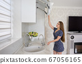 Young woman at luxury modern classic white kitchen interior 67056165