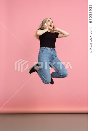 Portrait of young caucasian woman with bright emotions on coral pink studio background 67058933